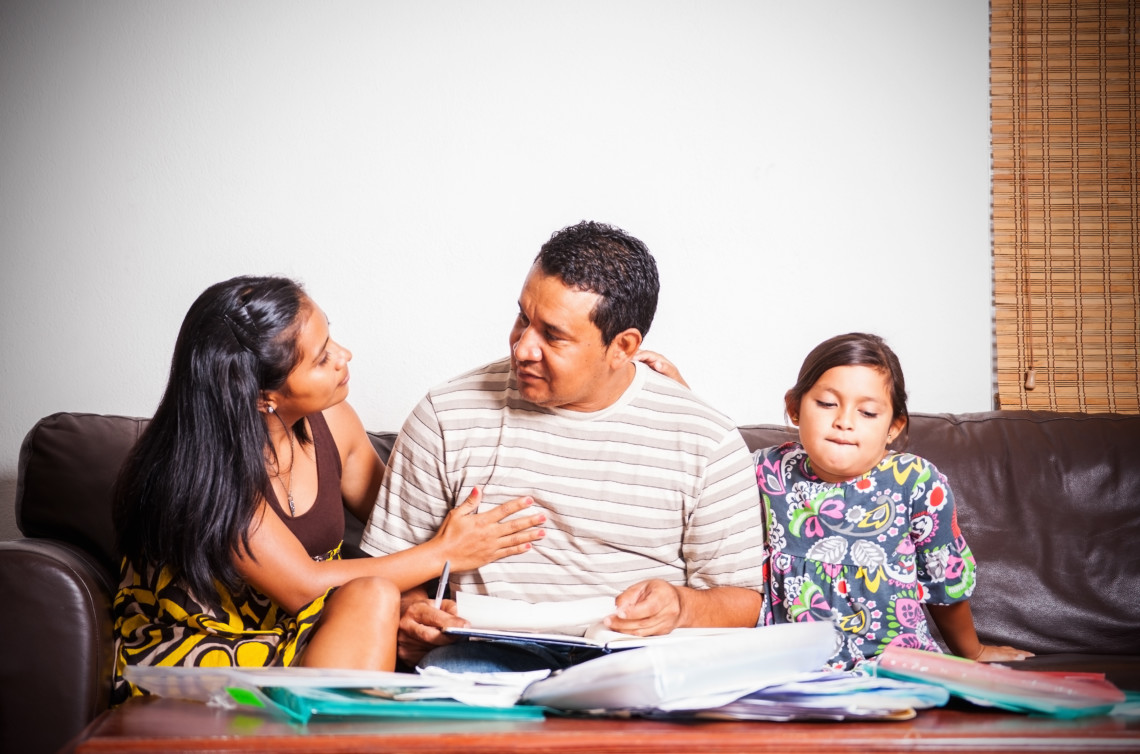A photograph of a Latino family struggling with debts. A concept for bankruptcy and foreclosure.